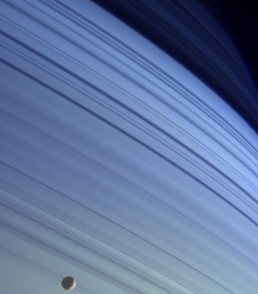 Mimas drifts along in its orbit against the azure backdrop of Saturn's northern latitudes in this true color view. The long, dark lines on the atmosphere are shadows cast by the planet's rings.