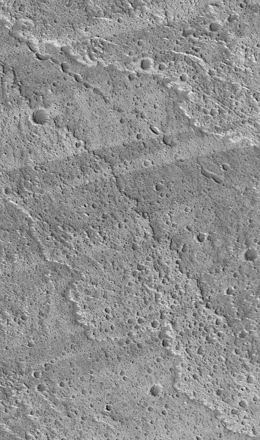 NASA's Mars Global Surveyor shows alternating light and dark wind streaks superimposed over a rugged lava flow surface on the west flank of the volcano, Ascraeus Mons on Mars.