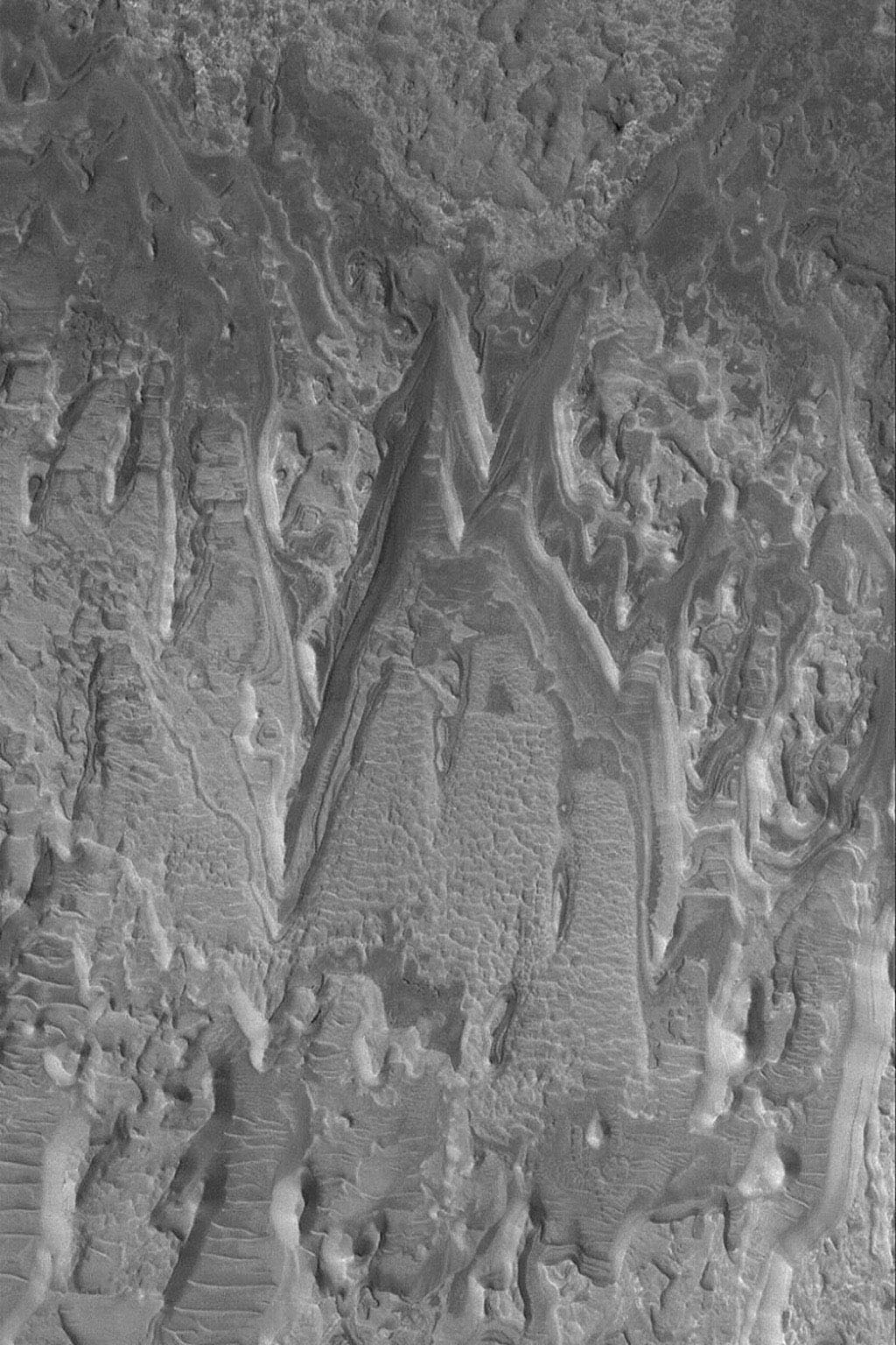 NASA's Mars Global Surveyor shows eroded layer outcrops in a crater in Terra Tyrrhena on Mars where exposures of layered, sedimentary rock are common.