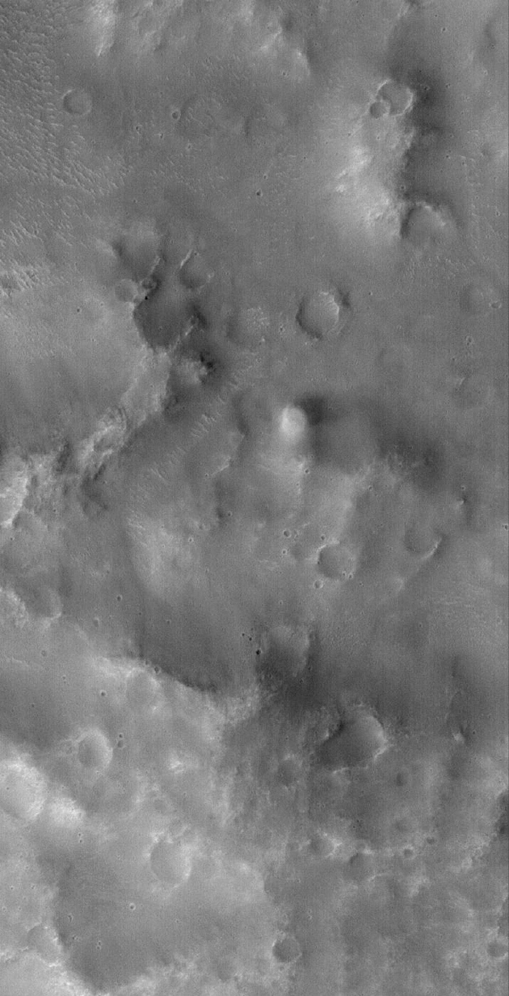 NASA's Mars Global Surveyor shows a fuzzy, nearly-circular bright, active dust devil making its way across the rugged terrain of the Loire Vallis system on Mars.