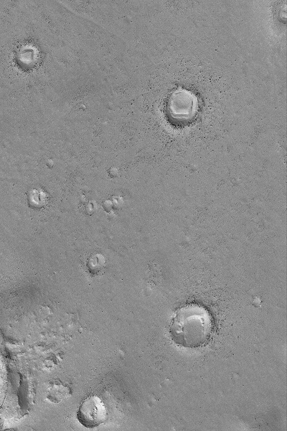 NASA's Mars Global Surveyor shows several north mid-latitude meteor impact craters on Mars with bouldery ejecta deposits. Each of the craters was once buried and later exhumed.