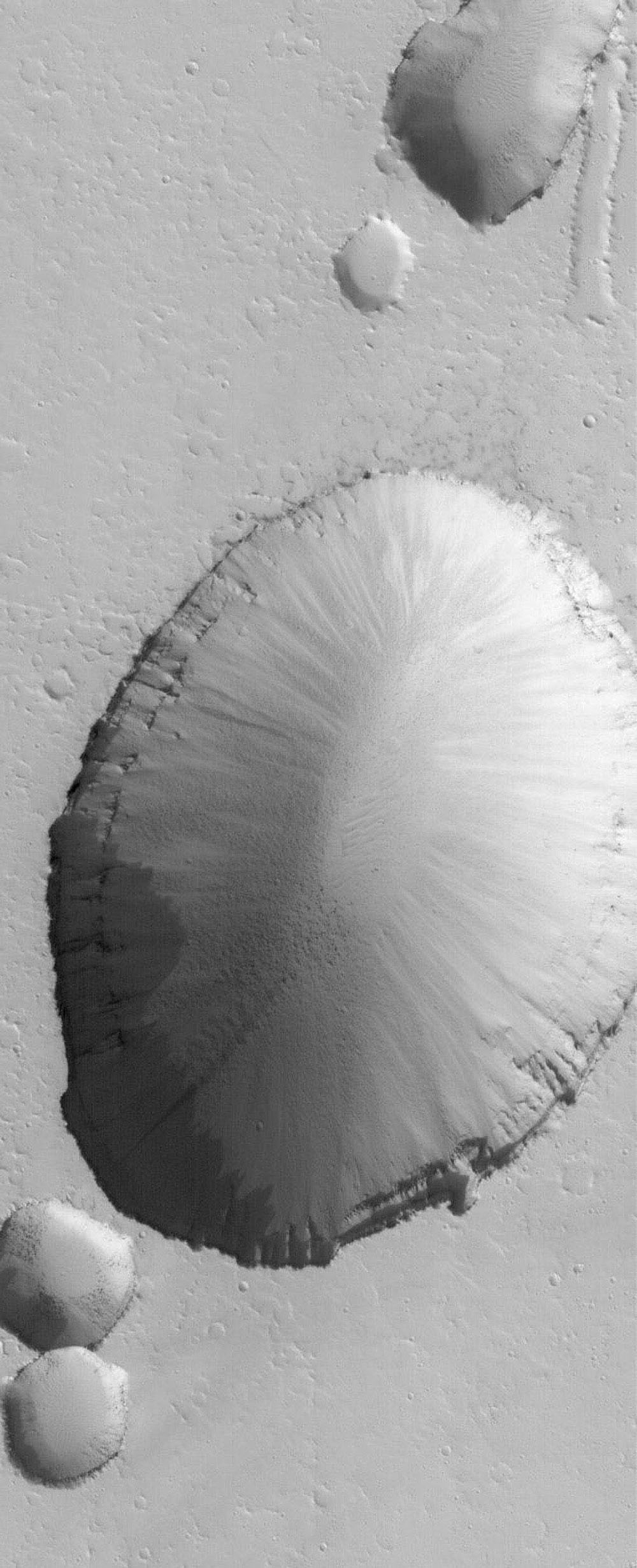 NASA's Mars Global Surveyor shows a large collapse pit (and portions of several smaller pits) in the Tractus Fossae portion of the Tharsis region of Mars.