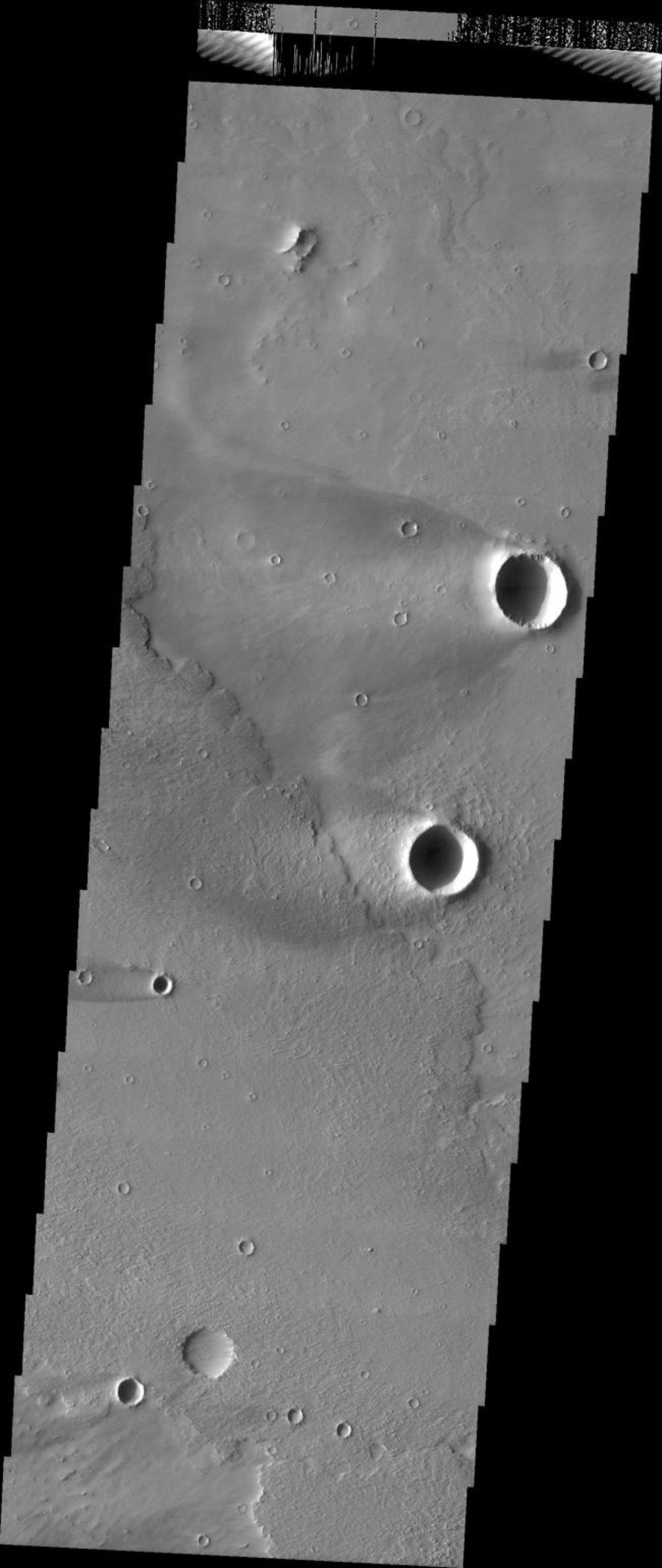 This image released on July 13, 2004 from NASA's 2001 Mars Odyssey shows windstreaks are features caused by the interaction of wind and topographic landforms on Mars such as two large windstreaks of the scour-and-deposit type.