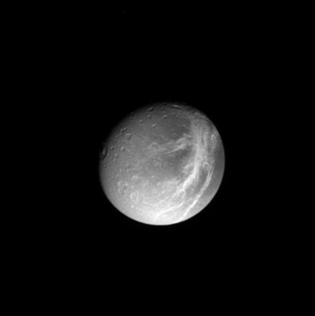 A gorgeous Dione poses for NASA's Cassini spacecraft, with shadowed craters and bright wispy streaks first observed by the Voyager spacecraft 24 years ago.