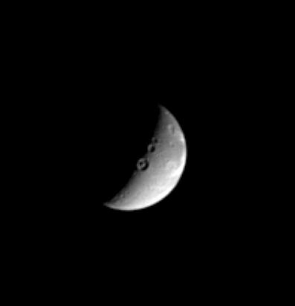 This image captured by NASA's Cassini spacecraft shows three sizeable impact craters, including one with a marked central peak, lie along the line that divides day and night on the Saturnian moon, Dione.
