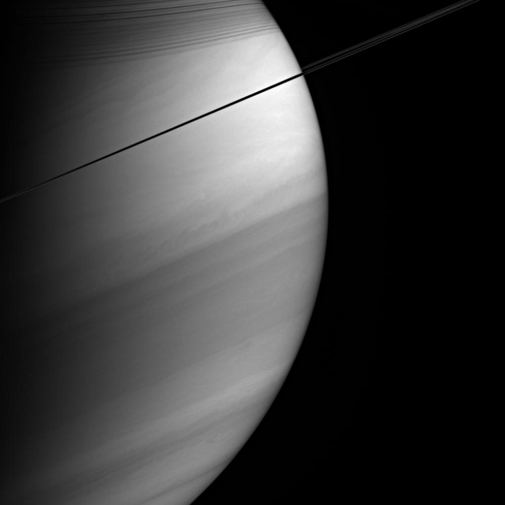 Viewed nearly edge-on, Saturn's rings appear dark and pencil-thin against the backdrop of the planet's swirling clouds. This image was taken with NASA's Cassini spacecraft's wide-angle camera on Feb. 18, 2005.