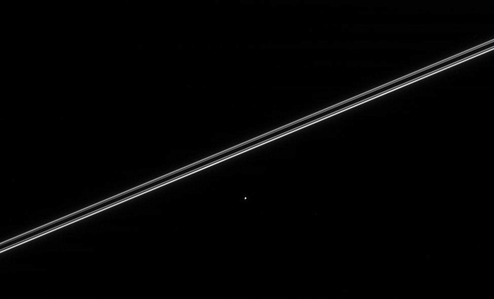 Saturn's moon Helene, seen here with Saturn's nearly edge-on rings, orbits 60 degrees ahead of Dione and is called a 'Trojan' moon. This image was taken in visible light with NASA's Cassini spacecraft's narrow-angle camera on March 12, 2005.