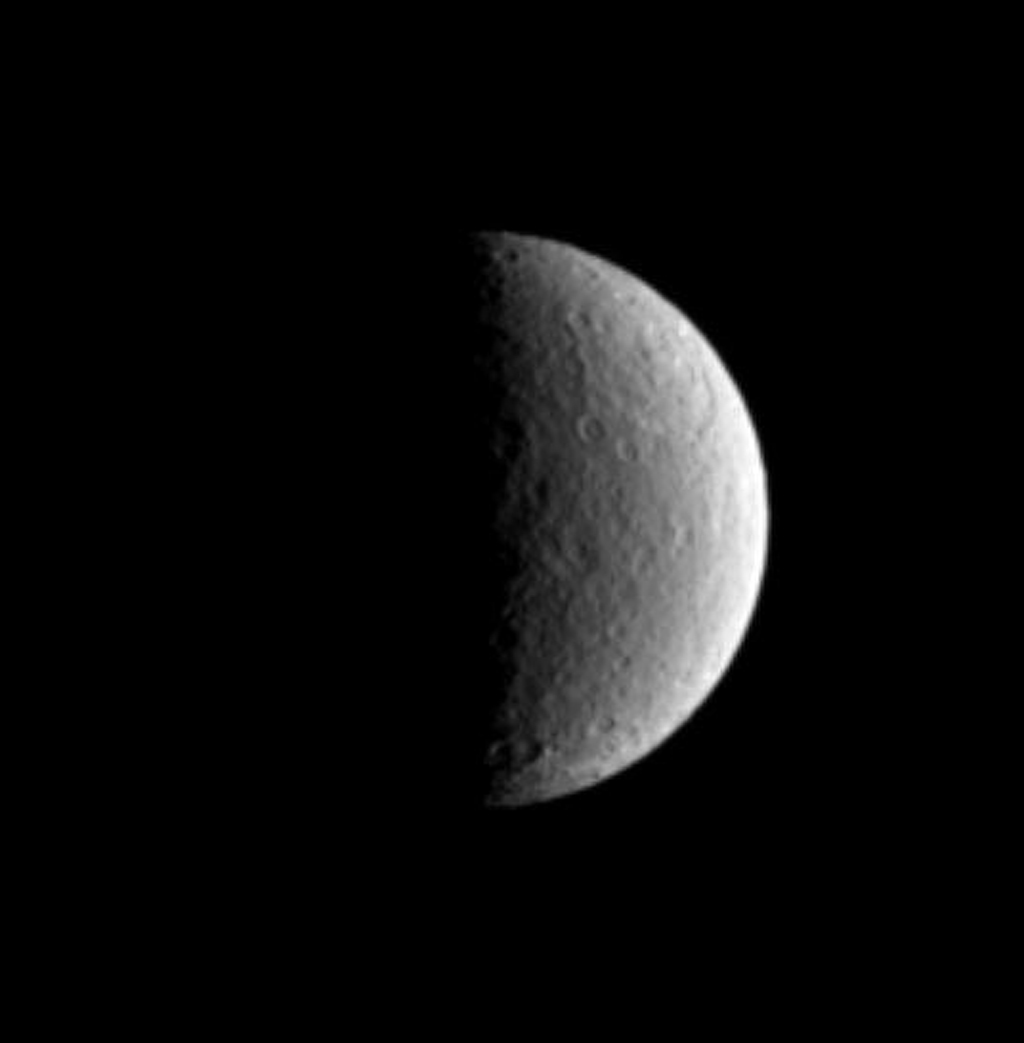 The large Tirawa impact basin on Saturn's moon Rhea is visible at the two o'clock position in this image captured by NASA's Cassini spacecraft.