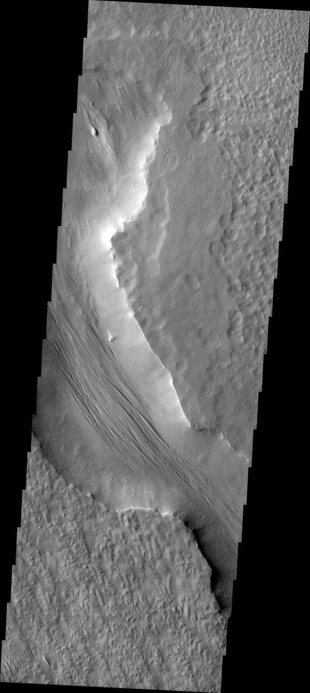 This image released on July 17, 2004 fromNASA's 2001 Mars Odyssey shows that eons of atmospheric dust storm activity has left its mark on the surface of Mars. Yardangs form in channel floor deposits.