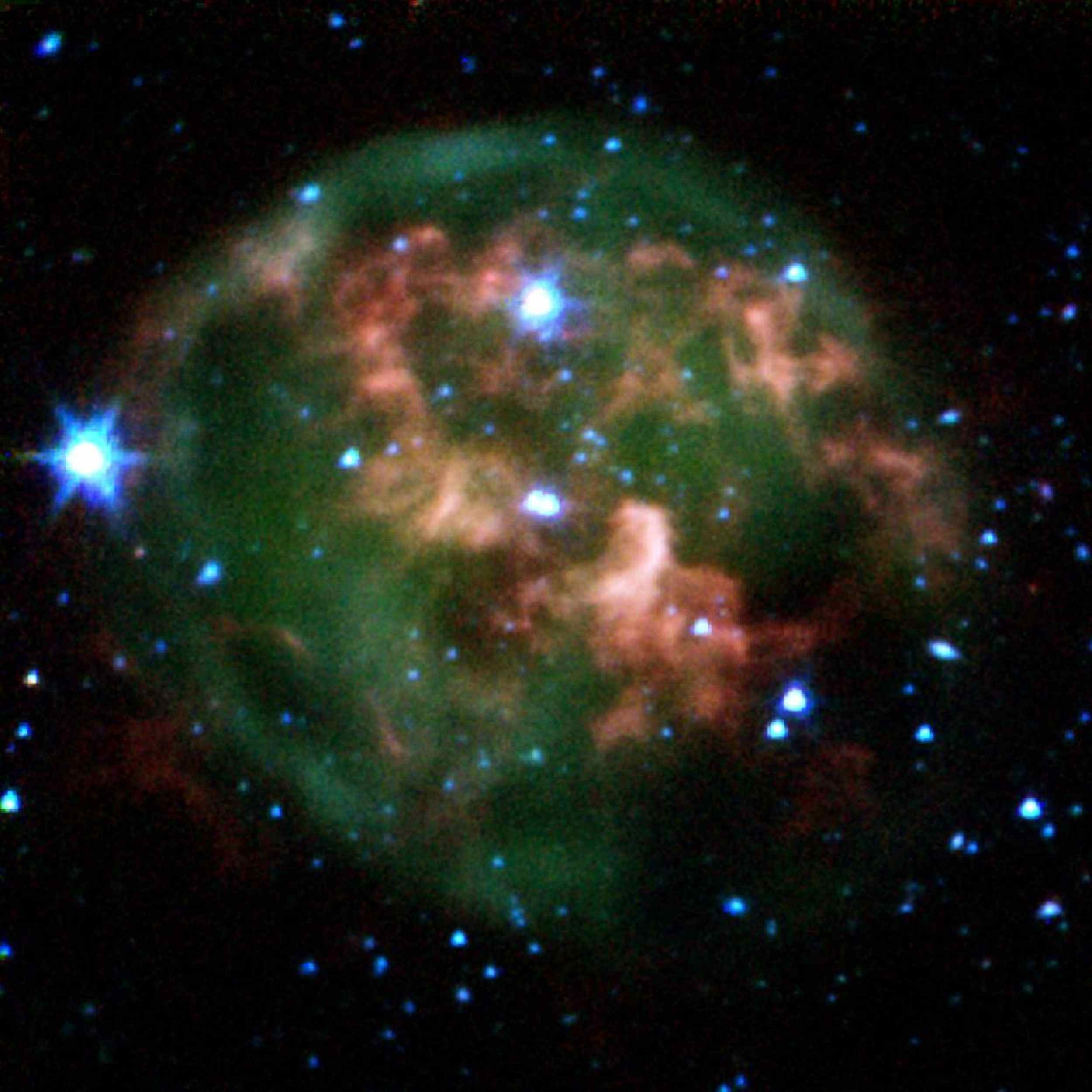 This false-color image from NASA's Spitzer Space Telescope shows a dying star (center) surrounded by a cloud of glowing gas and dust.