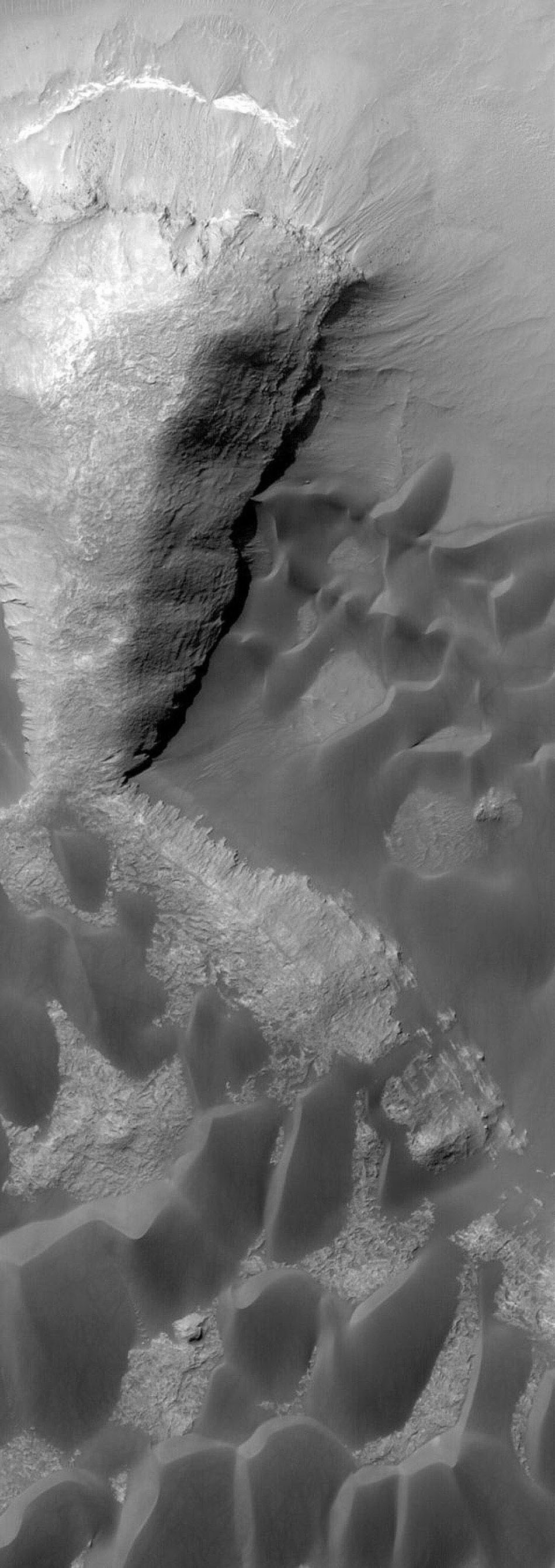 NASA's Mars Global Surveyor shows dark sand dunes and layered rock outcrops in Rabe Crater on Mars.
