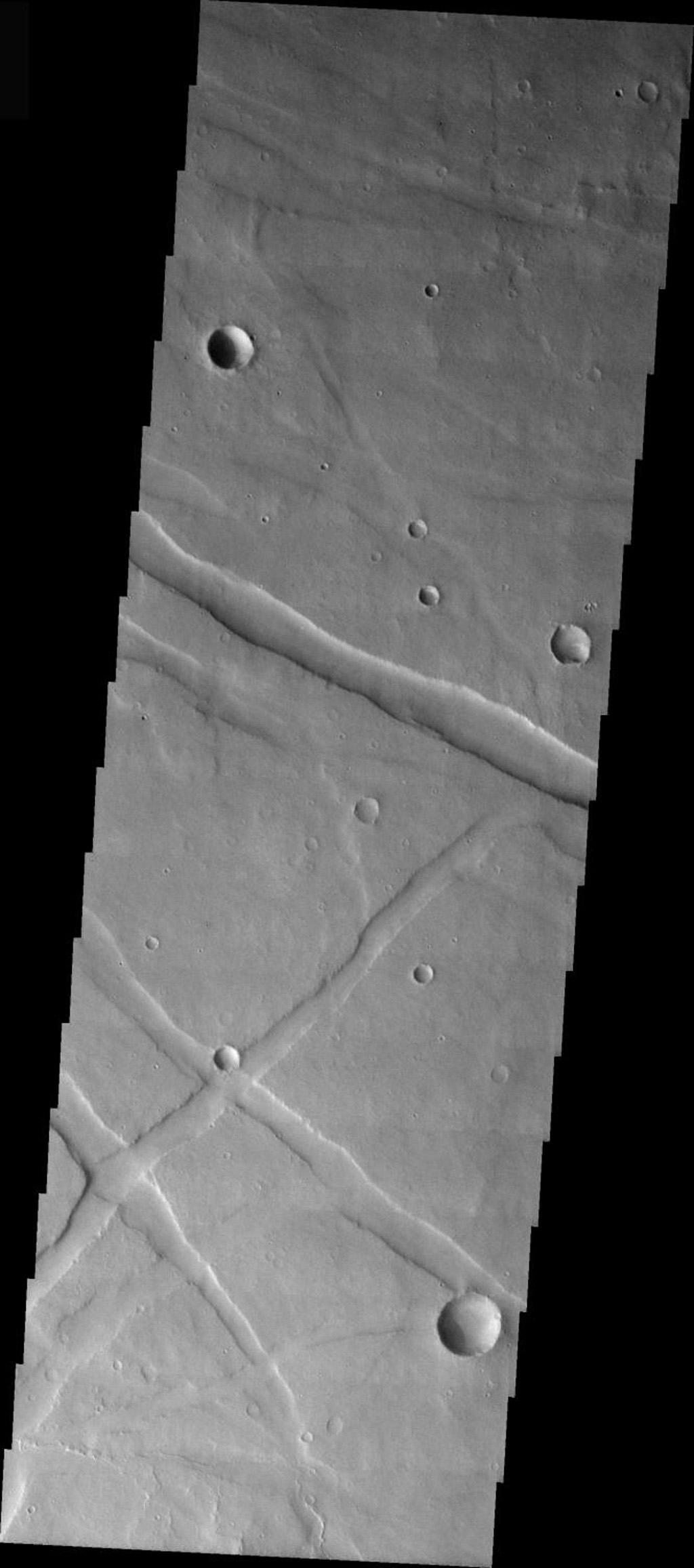 This image from NASA's 2001 Mars Odyssey shows the south of the rim of Valles Marineris on Mars. The troughs seen in this image are structural features called graben.