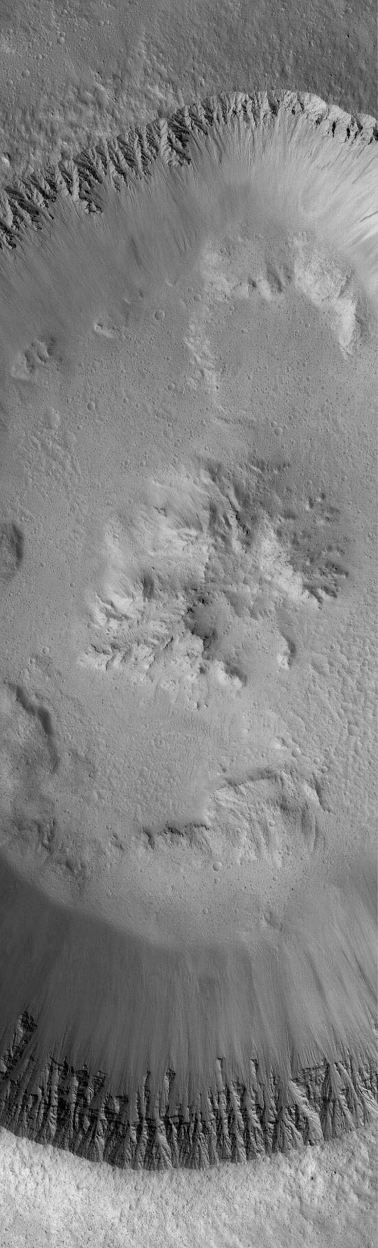 NASA's Mars Global Surveyor shows fine details in the walls and floor of a meteor impact crater located immediately west of the Lycus Sulci ridged terrain on Mars. The walls of the crater exhibit the finely-detailed layering of the local bedrock.