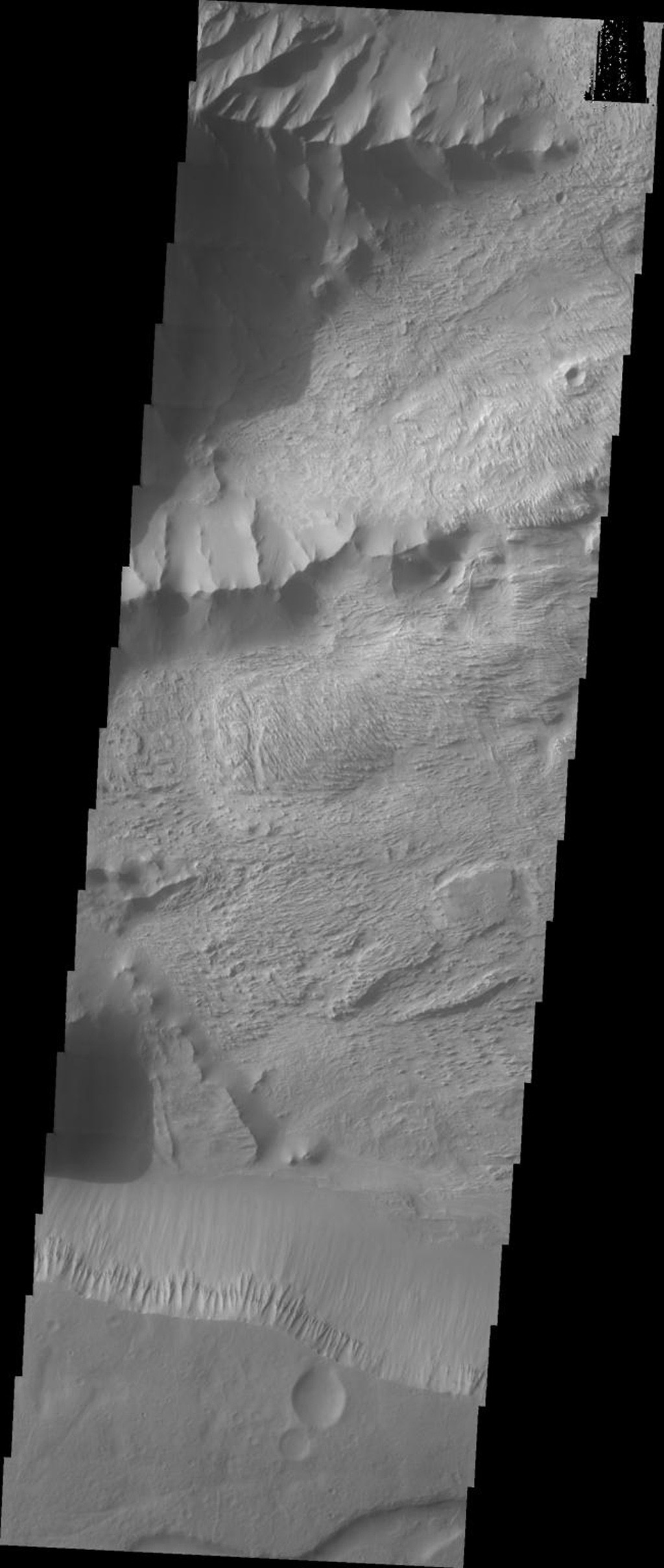 This image released on Sept 27, 2004 from NASA's 2001 Mars Odyssey shows a part of Candor Chasma on Mars. Wind etched surfaces are dominant on this picture, but gullies and layered rock formations are also present in this area.