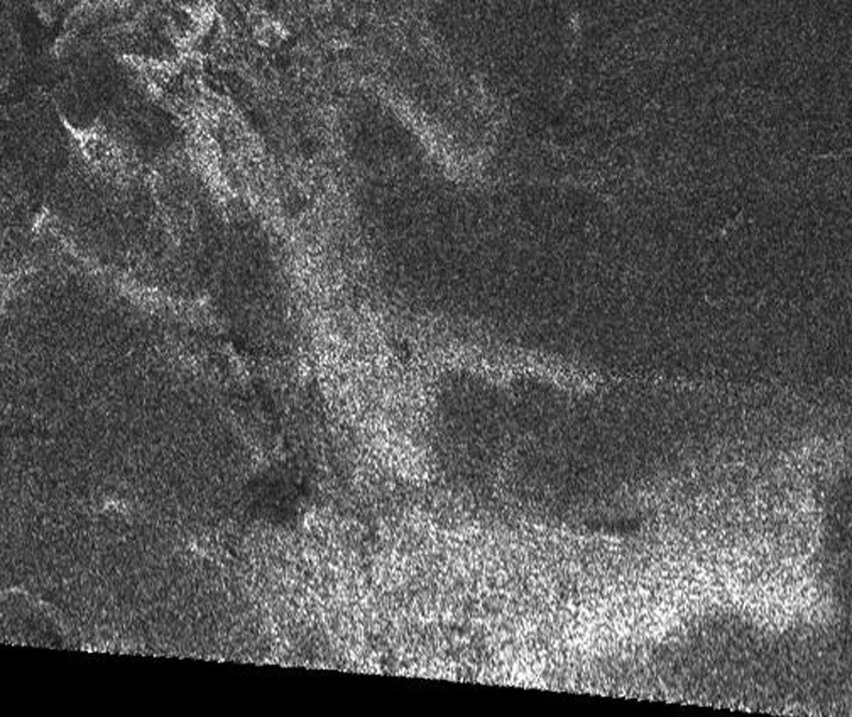 This synthetic aperture radar image of the surface of Saturn's moon Titan was acquired on Oct. 26, 2004, when NASA's Cassini spacecraft flew over. Dark regions may represent areas that are smooth, made of radar-absorbing materials.