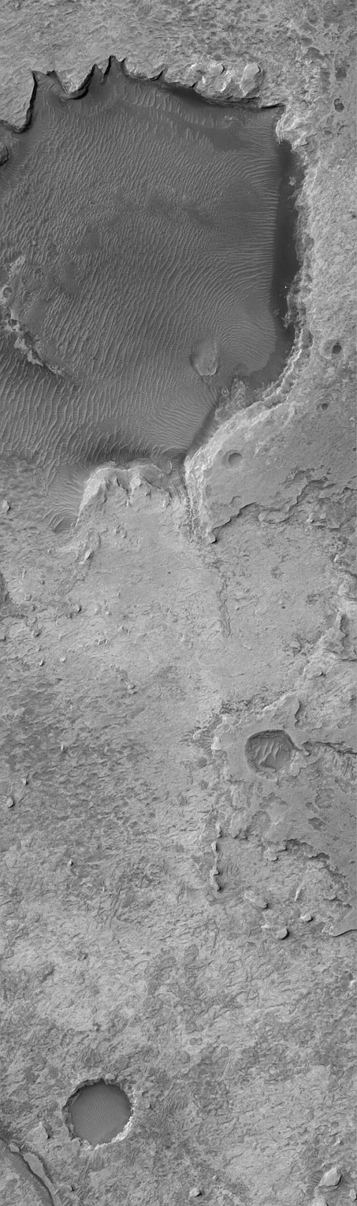 NASA's Mars Global Surveyor shows Sinus Meridiani, the site of the largest outcropping of light-toned, layered sedimentary rocks on Mars. Sedimentary rocks are covered by a regolith of windblown sand and granules.