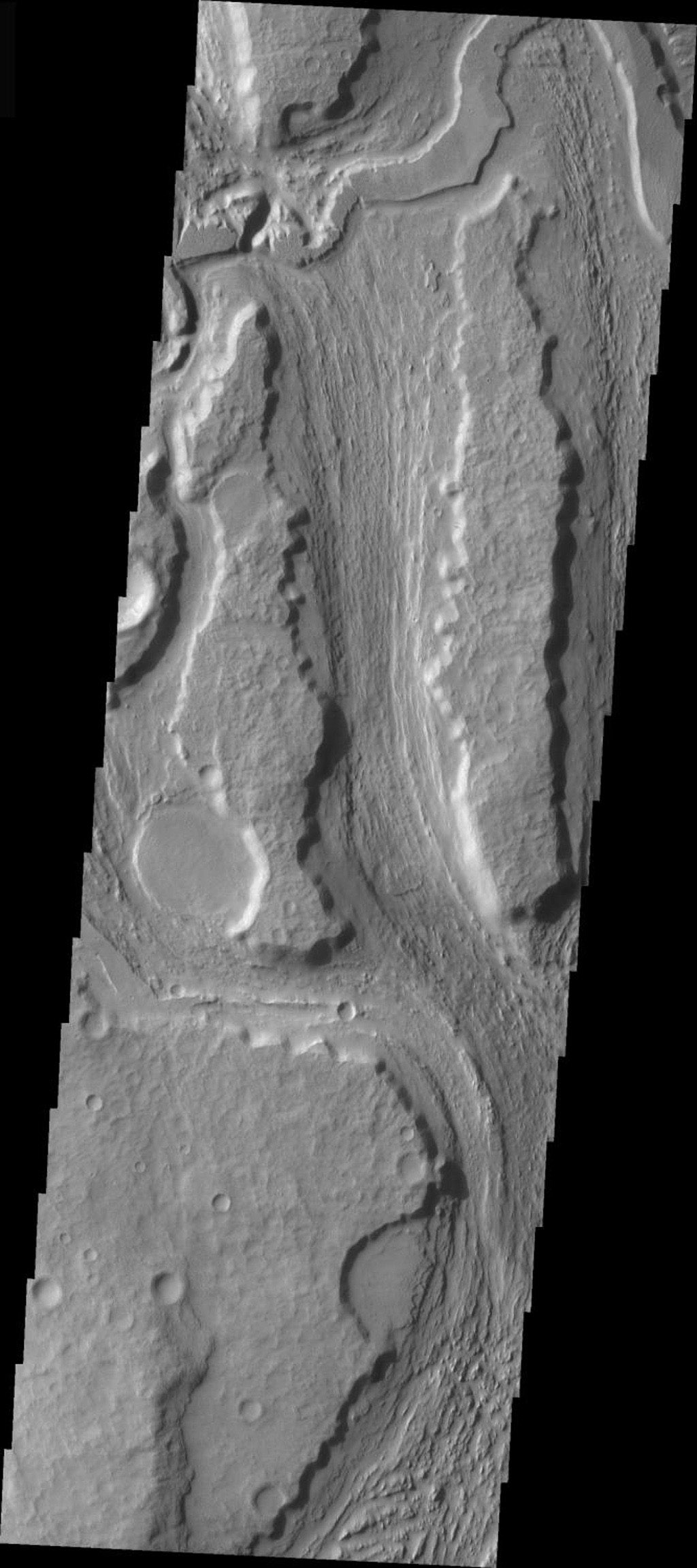 This image released on Nov 29, 2004 from NASA's 2001 Mars Odyssey shows the southern reach of Minio Vallis on Mars, a small fluvial channel located near the larger Mangala Vallis. Both channels are in the Tharsis region, in the area west of Arsia Mons.