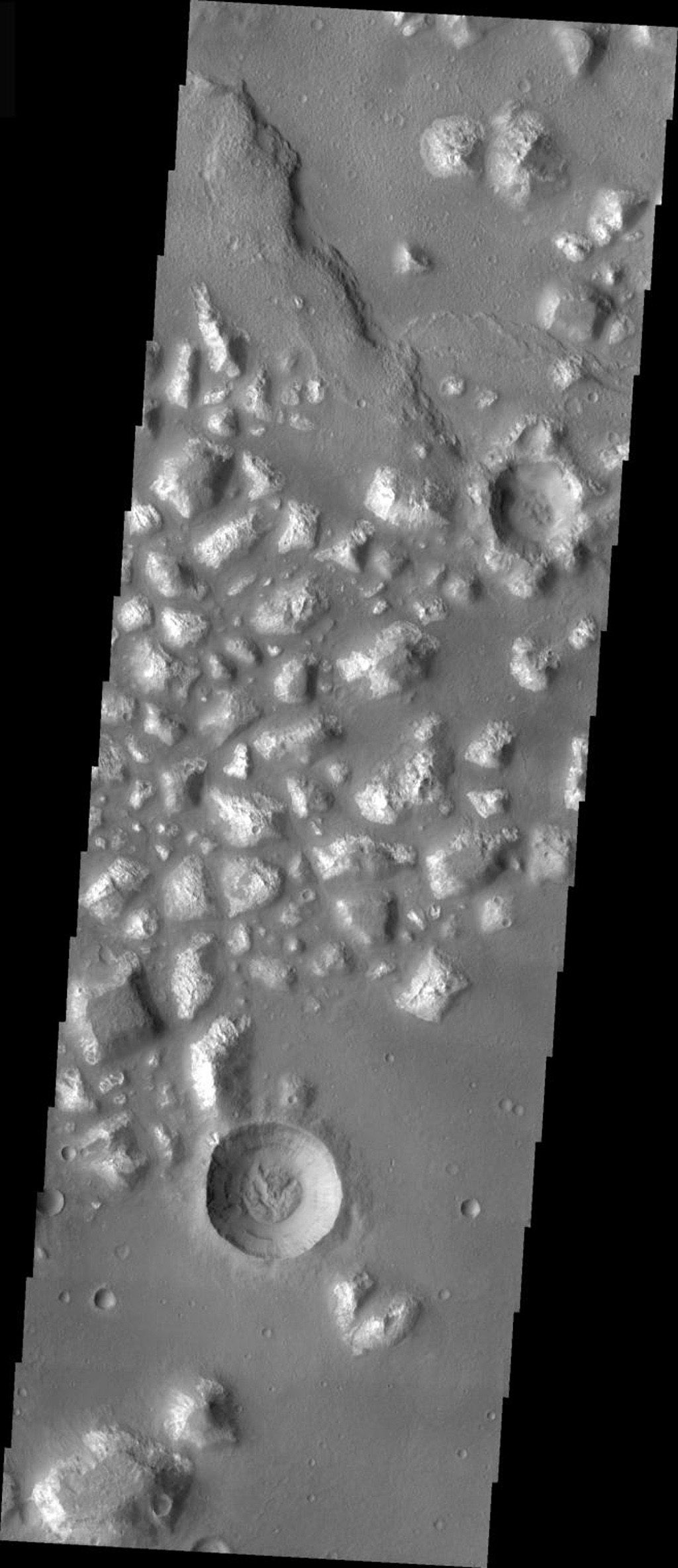 This image from NASA's Mars Odyssey is of a crater on Mars, located in Mare Chromium, showing evidence of exterior modification, with little interior modification. While the rim is still visible, the ejecta blanket has been removed or covered.