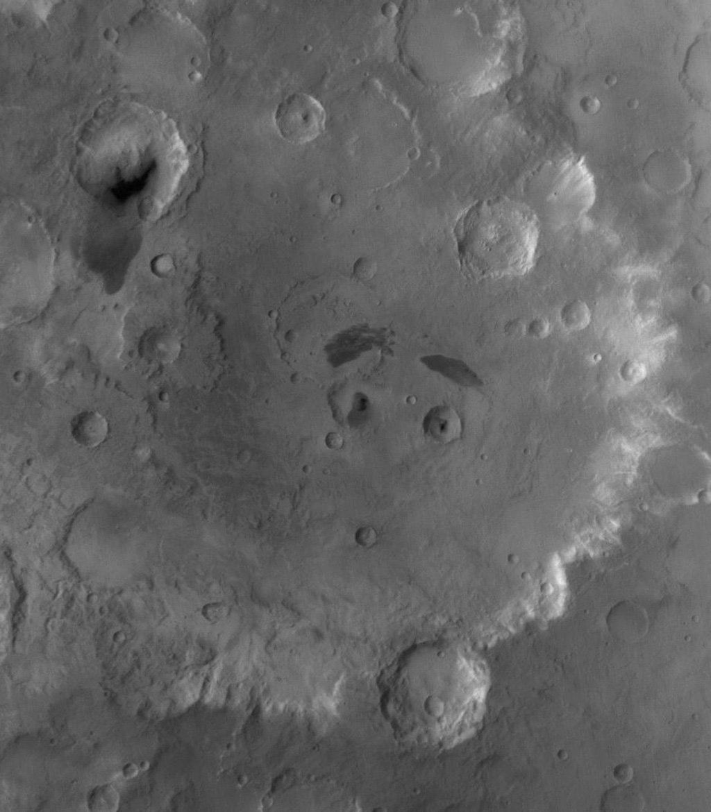 NASA's Mars Global Surveyor shows Tikhonravov Crater in central Arabia Terra on Mars. Two impact craters at its center that have dark patches of sand in them, giving the impression of pupils in two eyes.