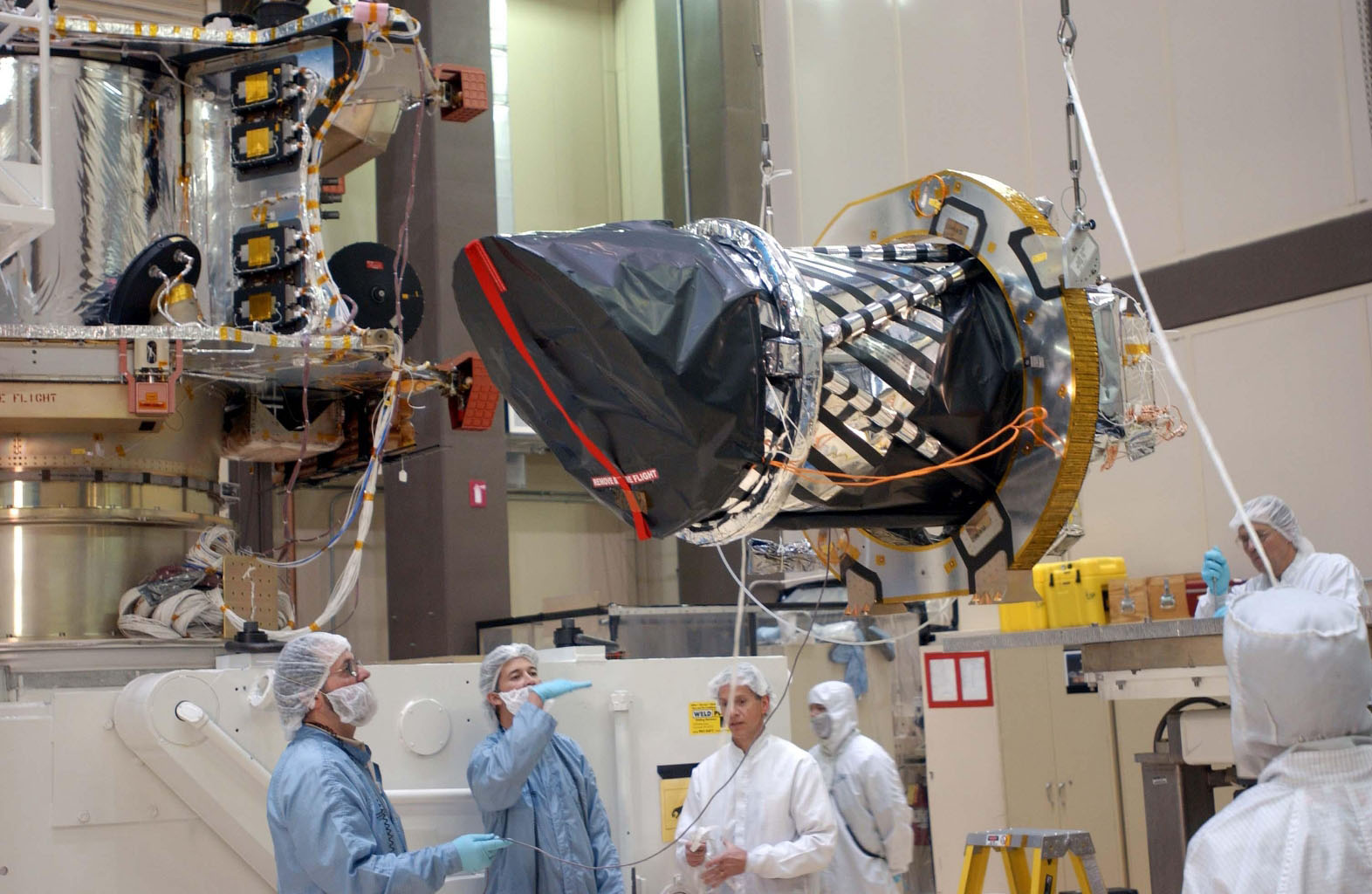Workers at Lockheed Martin Space Systems, Denver, hoist a telescopic camera for installation onto NASA's Mars Reconnaissance Orbiter spacecraft on Dec. 11, 2004.