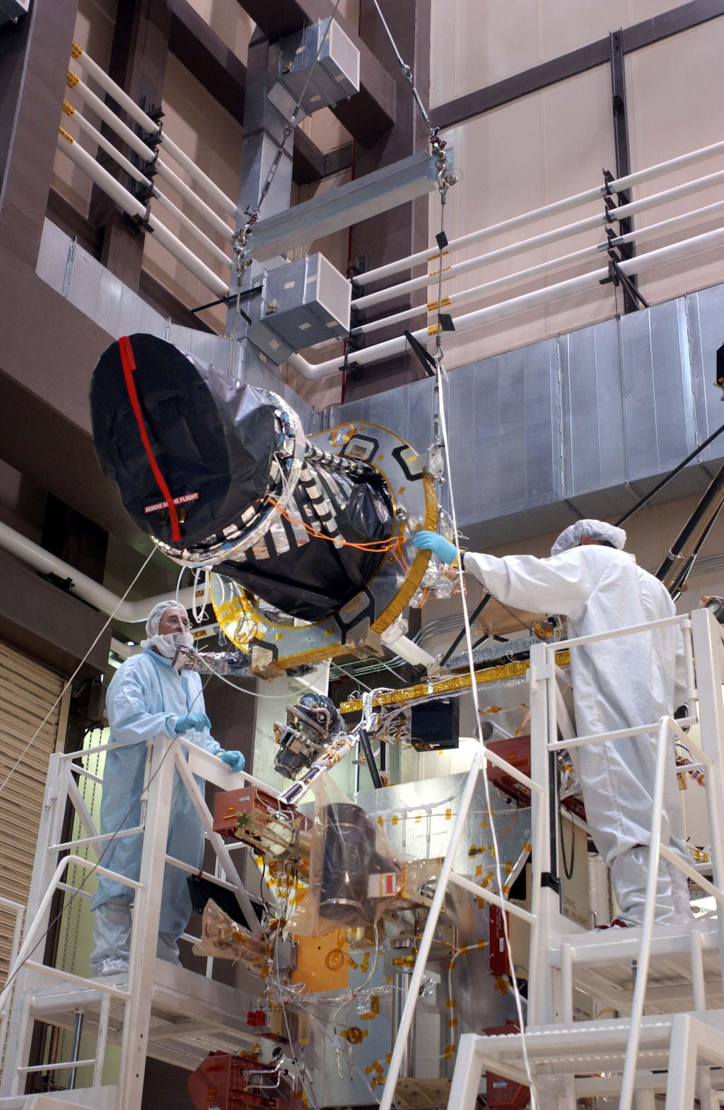 Workers at Lockheed Martin Space Systems, Denver, position a telescopic camera for installation onto NASA's Mars Reconnaissance Orbiter spacecraft on Dec. 11, 2004.