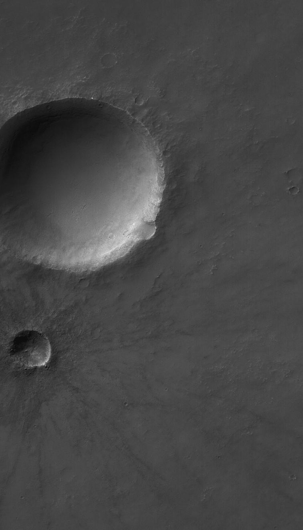NASA's Mars Global Surveyor shows several meteor impact craters on Solis Planum on Mars. The second-largest crater in this scene is relatively young and fresh, exhibiting arrayed ejecta pattern and numerous boulders near its rim.