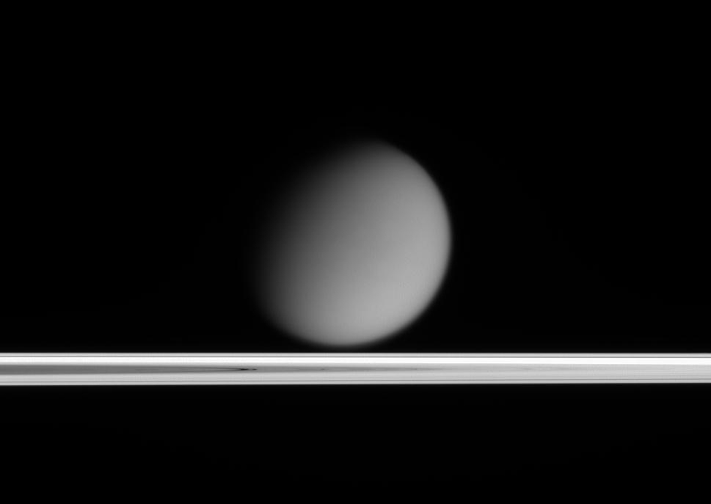Saturn's hazy moon Titan appears to drift above Saturn's ringplane in this view taken only a tenth of a degree above the rings. This image was taken in visible light with NASA's Cassini spacecraft's narrow-angle camera on March 25, 2005.