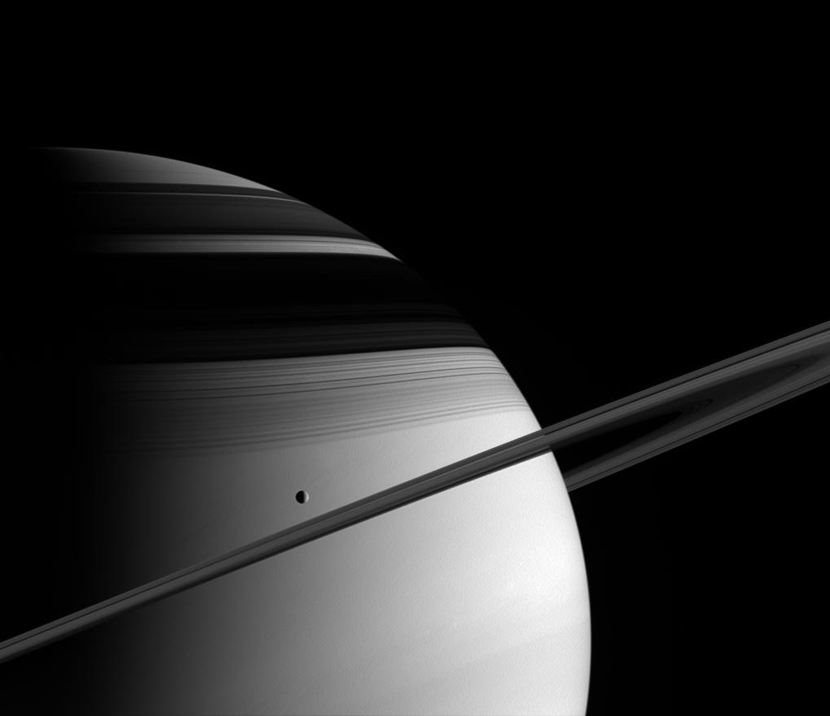 The majesty of Saturn overwhelms in this image from NASA's Cassini spacecraft. Saturn's moon Tethys glides past in its orbit, and the icy rings mask the frigid northern latitudes with their shadows.
