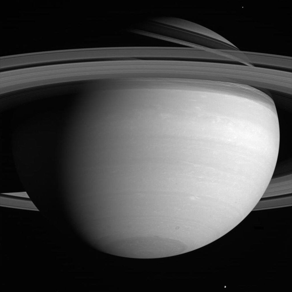 Far above the howling winds of Saturn, its icy moons circle the planet in silence. This image from NASA's Cassini spacecraft shows Mimas near the upper right, while Tethys hovers at the bottom.