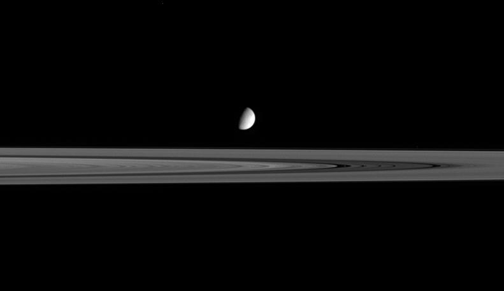 The moon Enceladus seems to hover above the outer reaches of Saturn's B ring. This image was taken in visible light with NASA's Cassini spacecraft's narrow-angle camera on Sept. 15, 2005.