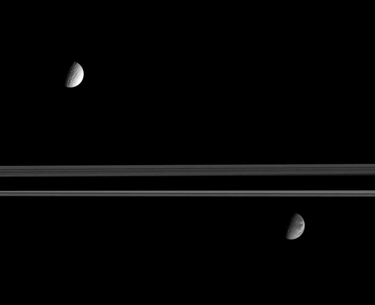 Saturn's expansive rings separate the moon's Tethys (at the top) from Dione (at the bottom). This image was taken in visible light with NASA's Cassini spacecraft's narrow-angle camera on Sept. 12, 2005.
