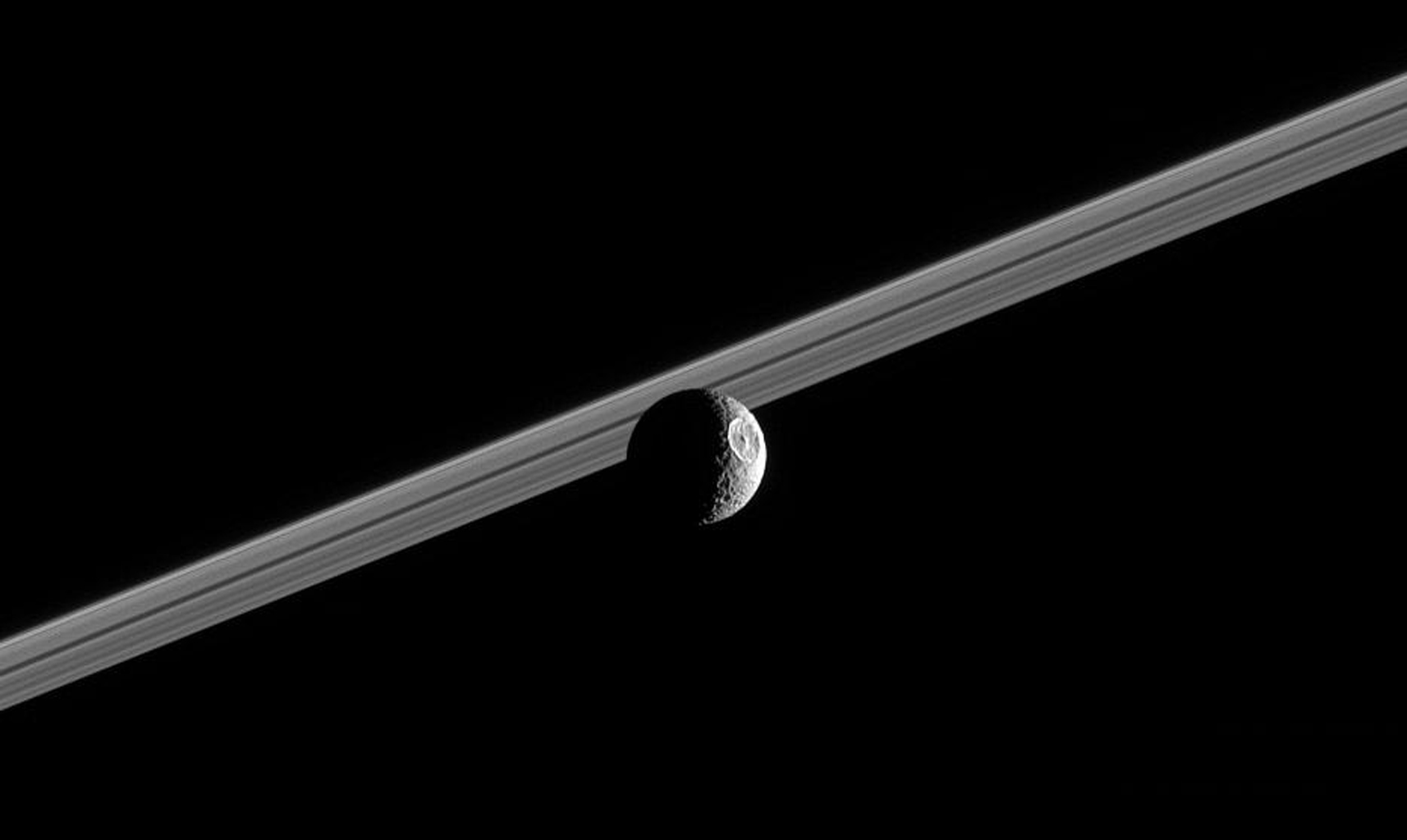 Impact-battered Mimas steps in front of Saturn's rings, showing off its giant 130-kilometer (80-mile) wide crater Herschel. This image was taken in visible green light with NASA's Cassini narrow-angle camera on Oct. 13, 2005.