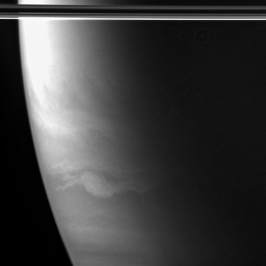 An oval-shaped feature, wider than Earth and with streamers extending out to the east and west, swirls in Saturn's southern hemisphere. This image was taken in wavelengths of polarized infrared light with NASA's Cassini spacecraft's wide-angle camera.
