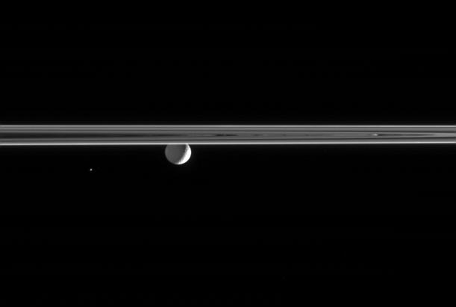 Gazing across the ringplane, NASA's Cassini spacecraft spots a Saturn-lit Mimas and the tiny Trojan moon Helene. Only the bright crescent on Mimas' eastern limb is lit by the Sun; the moon's night side is illuminated by Saturnshine.