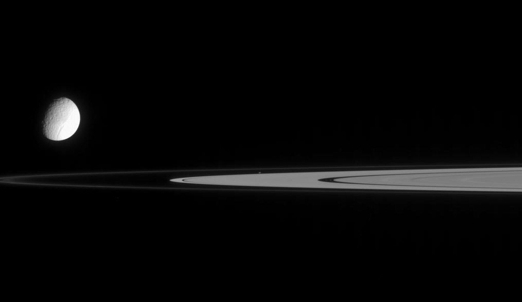 This view from NASA's Cassini spacecraft contains not one, but two moons. Tethys is slightly overexposed so that the real target of this image, tiny Atlas, can be seen. Atlas is at image center, just outside the A ring.