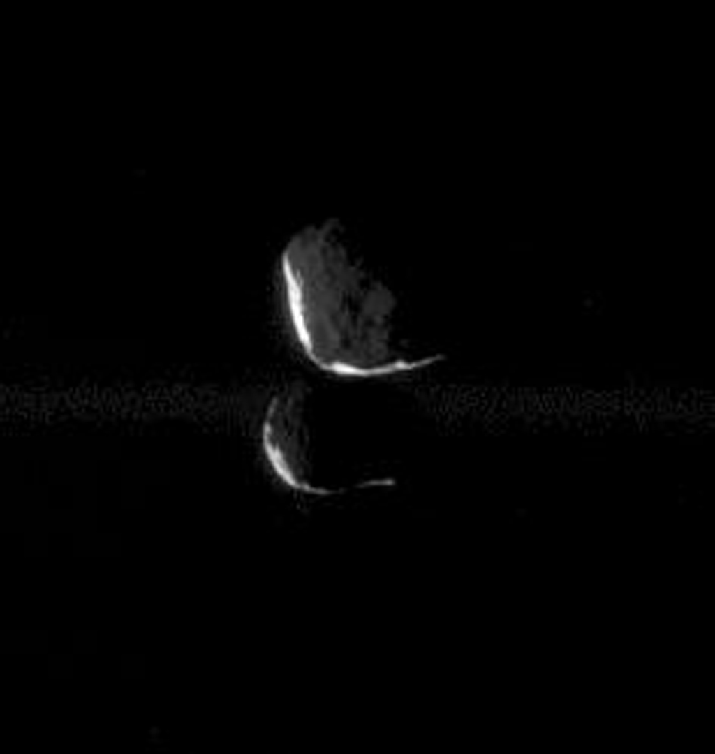 This close pairing of Janus and Epimetheus shows the two moons at 'high phase,' meaning that only a thin sliver of sunlit terrain is visible on each moon. This image was taken in visible light with NASA's Cassini spacecraft's narrow-angle camera.