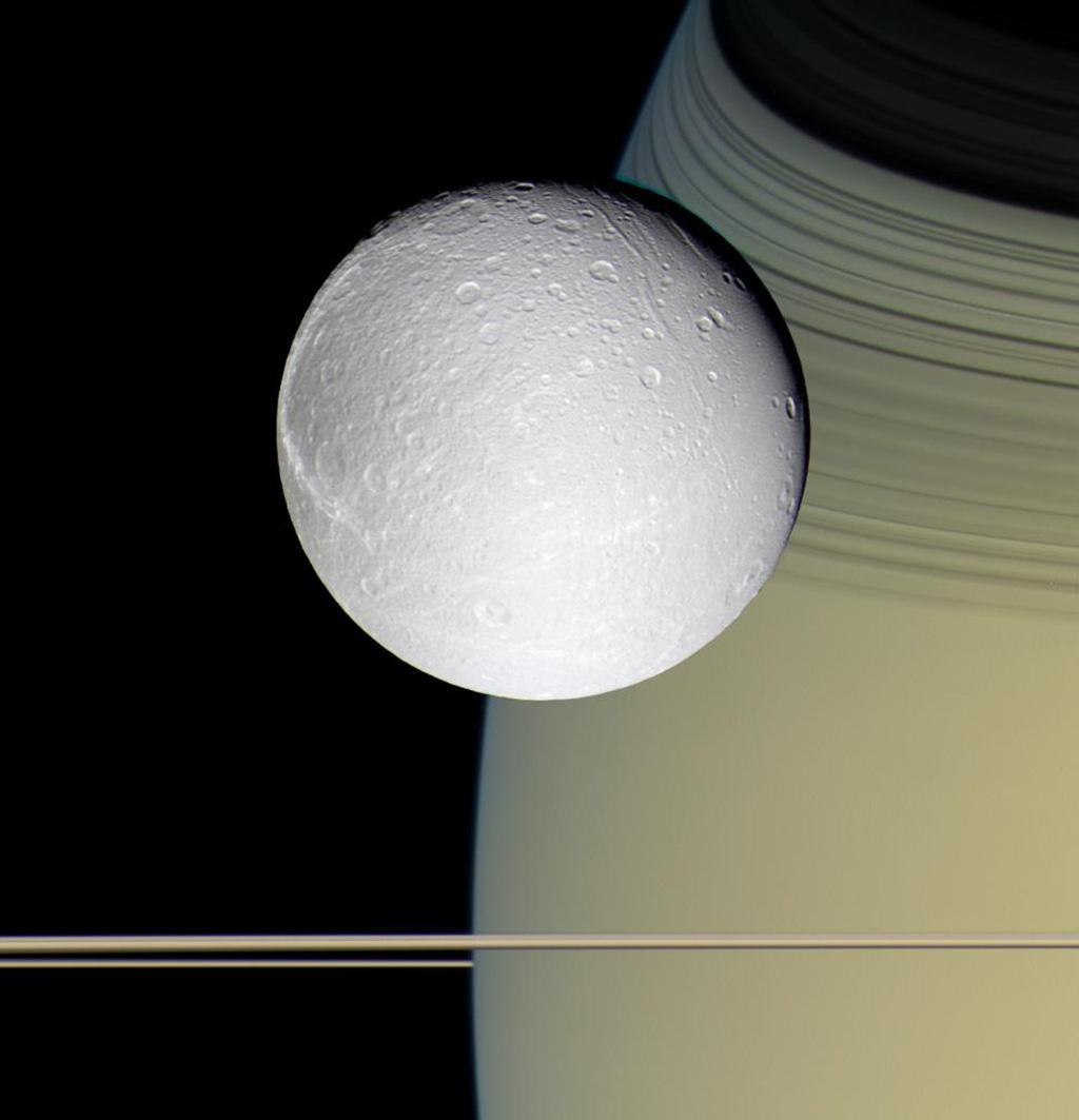 Speeding toward pale, icy Dione, Cassini's view is enriched by the tranquil gold and blue hues of Saturn in the distance. The horizontal stripes near the bottom of the image are Saturn's rings.