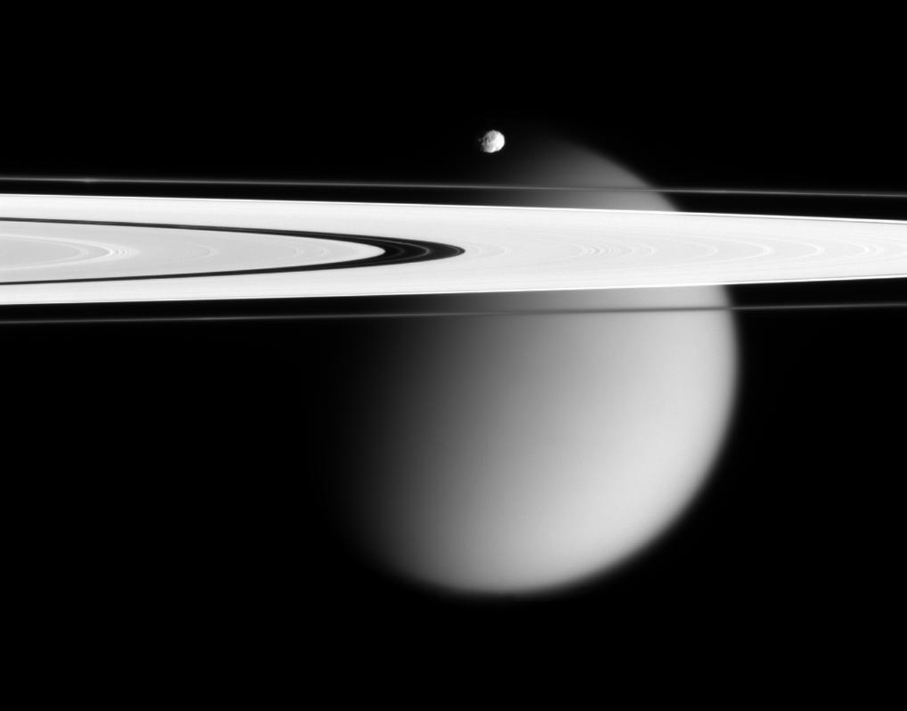 NASA's Cassini spacecraft delivers this stunning vista showing small, battered Epimetheus and smog-enshrouded Titan, with Saturn's A and F rings stretching across the scene.