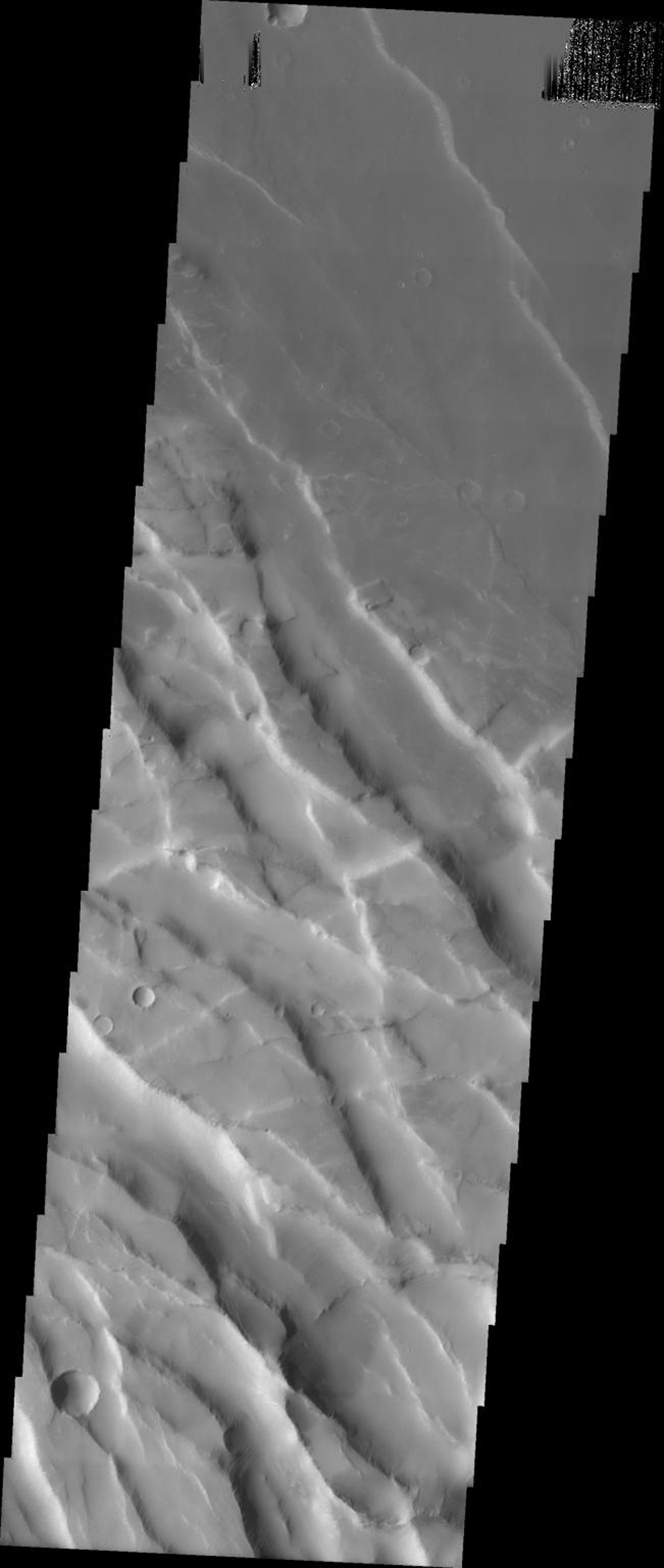 This image taken by NASA's Mars Odyssey shows graben in the region between Arsia Mons and Syria Planum on Mars. The older northeast trending graben have been cut by the younger southeast trending graben.