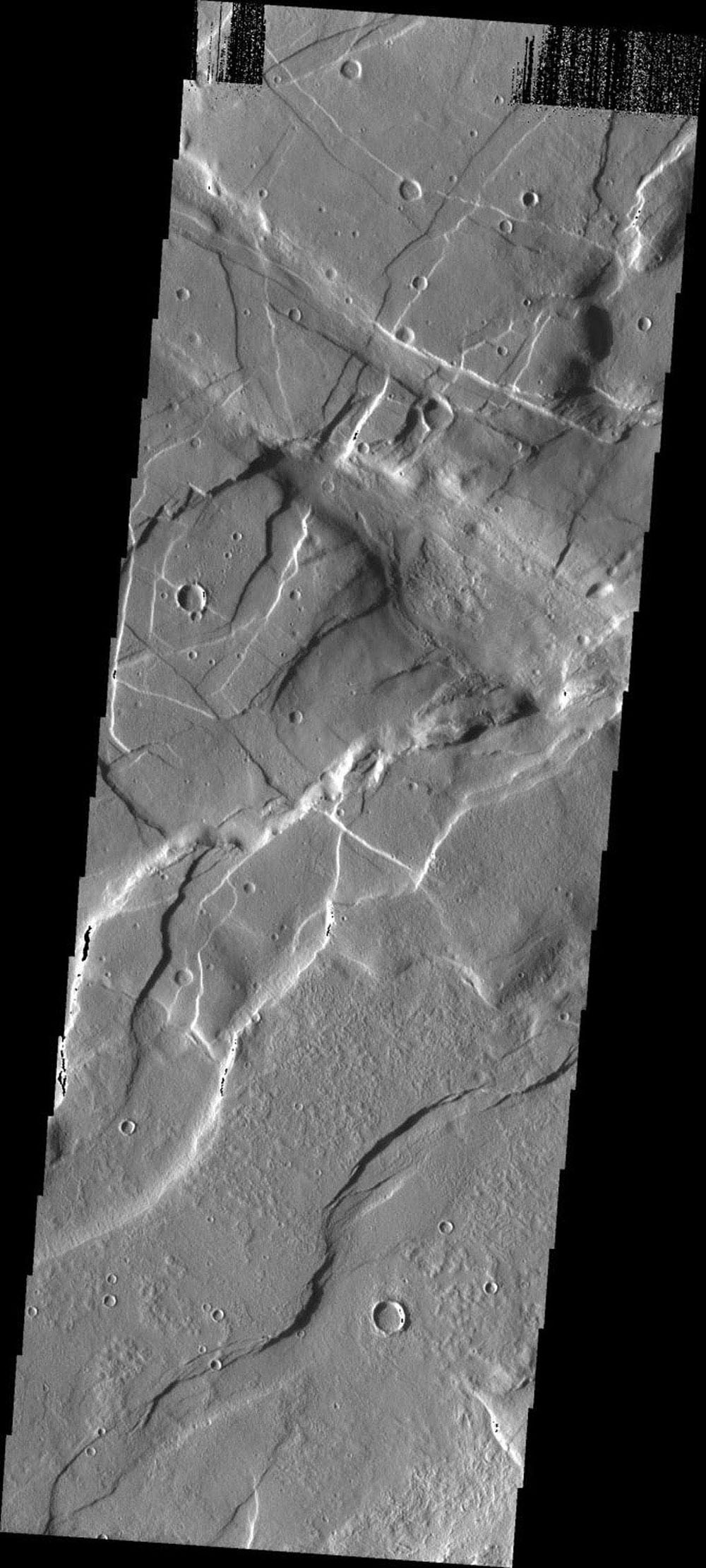 This image taken by NASA's Mars Odyssey shows the region east of Alba Patera on Mars featuring the complex relations that can occur in regions of multiple structural events. There are fractures and graben in this area that intersect at multiple angles.