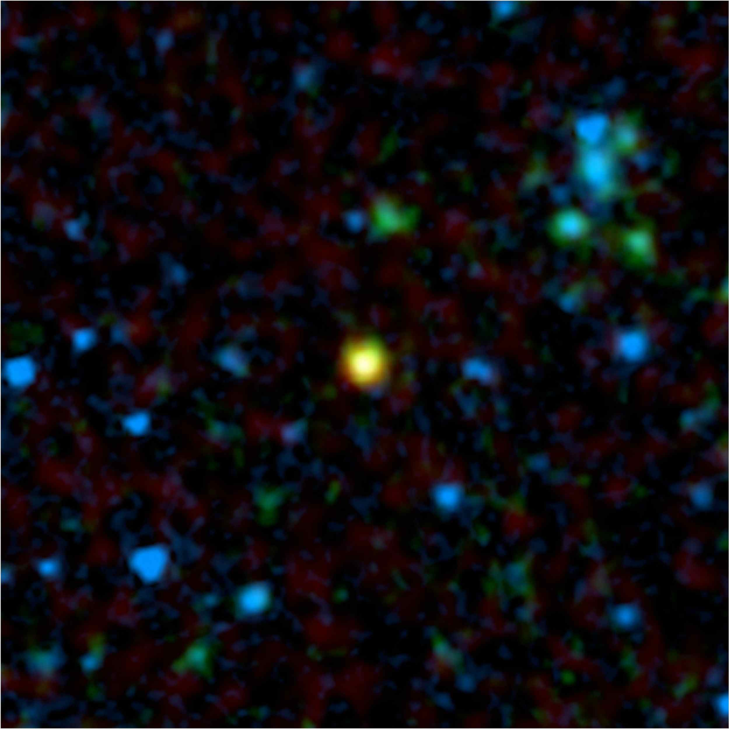 This false-color image from NASA's Spitzer Space Telescope shows a distant galaxy (yellow) that houses a quasar, a super-massive black hole circled by a ring, or torus, of gas and dust.