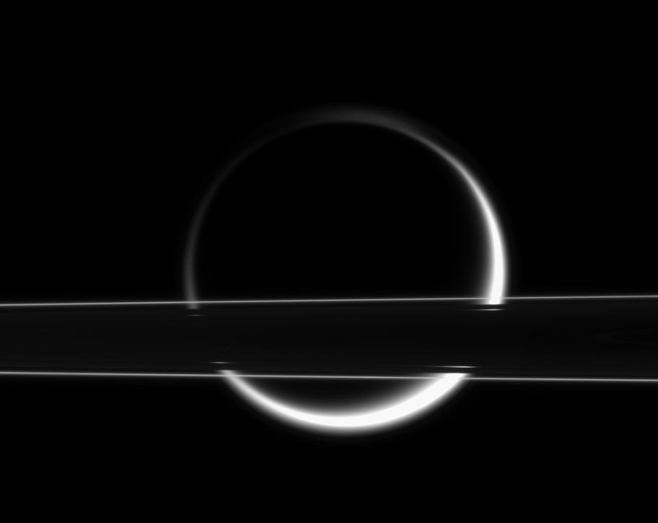 Titan's smoggy atmosphere glows brilliantly in scattered sunlight, creating a thin, gleaming crescent beyond Saturn's rings. This image was taken in visible light with NASA's Cassini spacecraft's narrow-angle camera on Jan. 18, 2006.