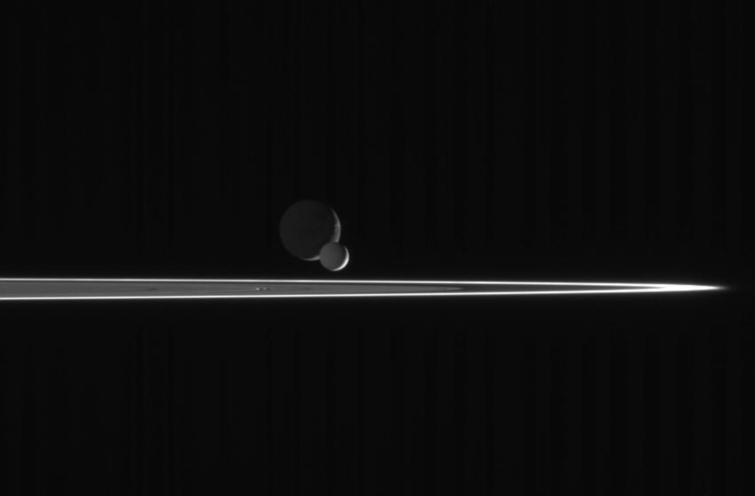 As our robotic emissary to Saturn, NASA's Cassini spacecraft is privileged to behold such fantastic sights as this pairing of two moons beyond the rings. The bright, narrow F ring is the outermost ring structure seen here.
