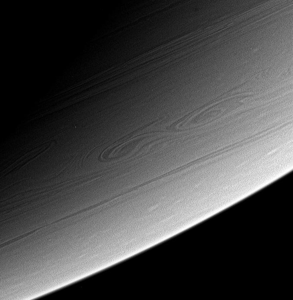 This view of high southern latitudes on Saturn shows very linear clouds at top, usually indicative of stable prevailing winds, and two turbulent, swirling features farther south. This image is from NASA's Cassini spacecraft