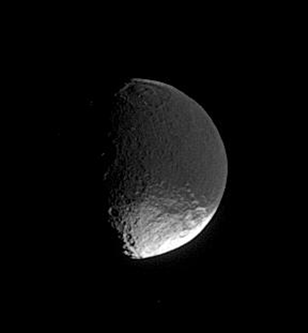 A distant glimpse of Iapetus reveals details within the dark terrain of Cassini Regio, including an impact basin at top that is roughly 400 kilometers (250 miles) wide. This is image is from NASA's Cassini spacecraft.