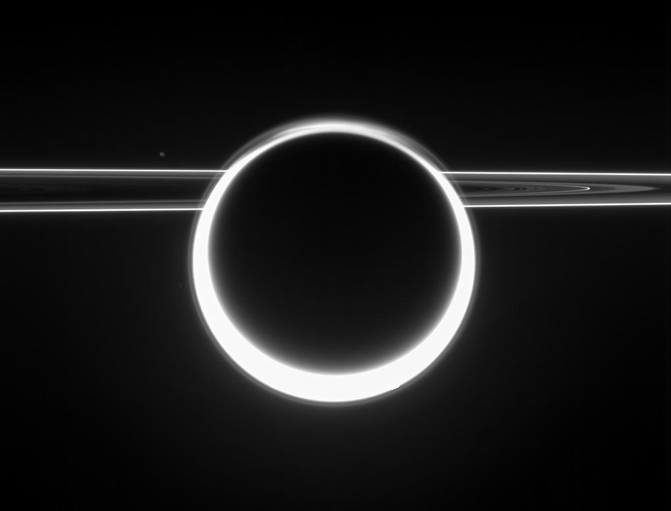 Dazzling Titan glows with a 360-degree sunset as light scatters through its very extended atmosphere. The rings show their unlit side to NASA's Cassini, as the spacecraft viewed them from slightly above the ringplane.