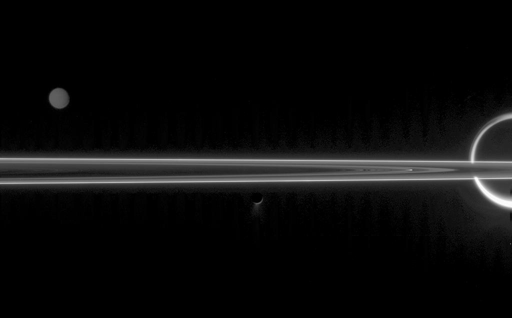 The real jewels of Saturn are arguably its stunning collection of icy moons. Seen here with the unlit side of the rings are Titan, Tethys and Enceladus with its fountain-like geysers. This image was captured by NASA's Cassini spacecraft.