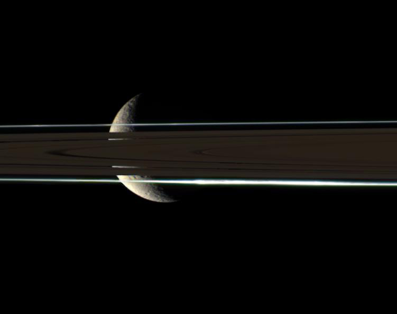 The rings cannot hide the ragged, icy crescent of Rhea, here imaged in color by NASA's Cassini spacecraft. The second-largest moon of Saturn shines brightly through gaps in the rings