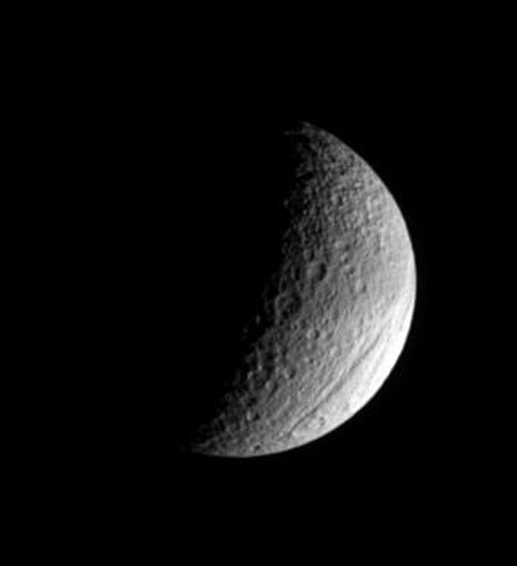 The ancient gorge of Ithaca Chasma carves a path across Saturn's moon, Tethys and continues out of sight over the moon's limb in this image from NASA's Cassini spacecraft.