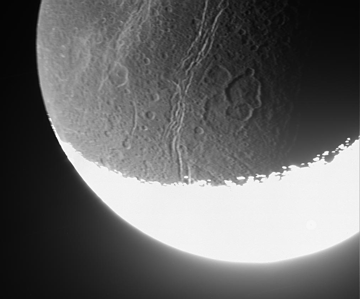 NASA's Cassini spacecraft whizzed past Dione on Aug. 16, 2006, capturing this slightly motion-blurred view of the moon's fractured and broken landscape in reflected light from Saturn.